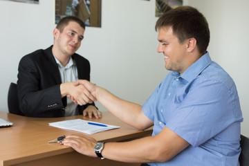 Smiling Businessmen Showing Handshake at Desk Area