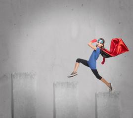 little girl wearing a superhero costume on a growing chart
