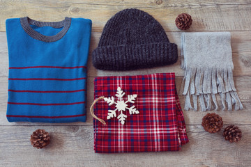 Winter clothes on wooden background. View from above