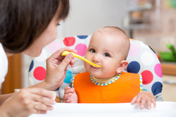 smiling baby eating food with mom on kitchen