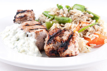 homemade tzatziki with grilled lamb kabobs, rice and vegetables.