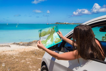 Young attractive woman with great map of island in the car