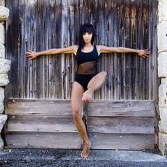 Danseuse pieds nus adossée à une porte en bois.