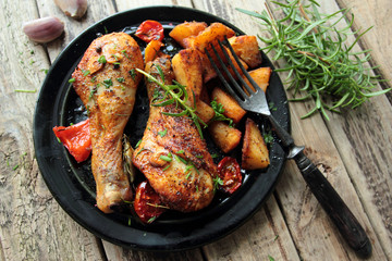 Roasted chicken legs with fried potatoes and fresh herbs