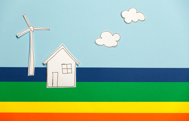 Home model, windmill and clouds on colorful background