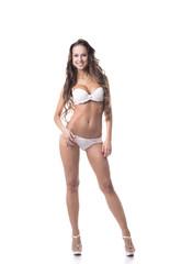 Smiling leggy girl posing in white erotic lingerie