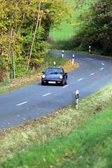 schneller Sportwagen auf Landstraße, herbstlich