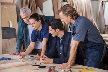 Carpenters Working On Blueprint
