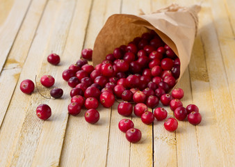 Cranberries in paper bag on yellow wooden background