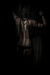 Fitness nude woman back through a curtain wire