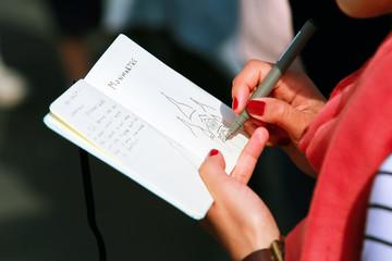 Girl draws in a notebook in Montmartre in Paris