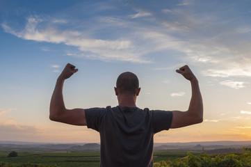 Man posing at sunset, sowing biceps. Nature background