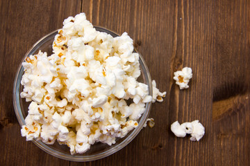 Popcorn in bowl on wooden table seen from above