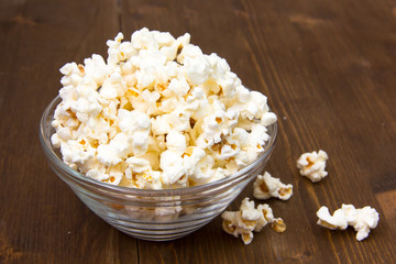 Popcorn in glass bowl on wooden table