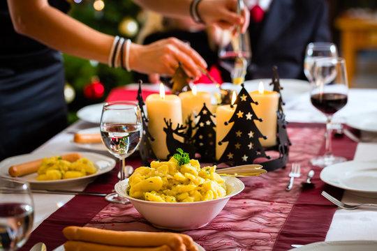 Familie bei Weihnachtsessen Würstchen und Kartoffelsalat
