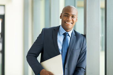 afro american businessman holding laptop computer