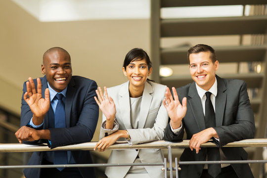 businesspeople waving in office