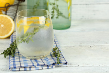 Tasty cool beverage with lemon and thyme, on wooden background