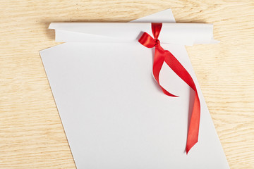 Scroll of paper with a red ribbon on a wooden surface.