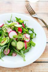 arugula, cucumber and radishes in a salad