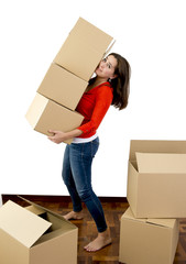 woman moving in a new house carrying cardboard boxes pile