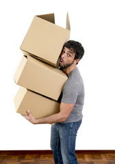 young man moving in new house carrying cardboard boxes pile