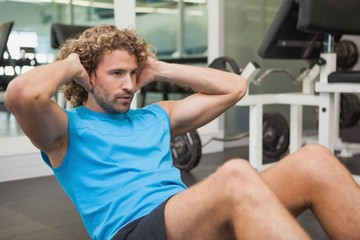 Handsome man doing abdominal crunches in gym