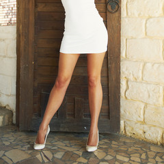 Sexy female legs in white fashion classical shoes.