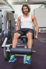 Handsome man doing leg workout at gym