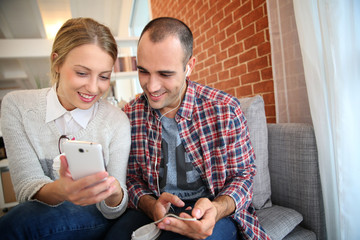 Friends having fun listening to music on smartphone