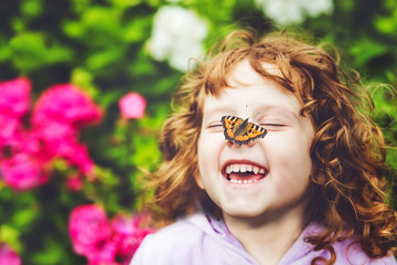 Laughing girl with a butterfly on his nose.