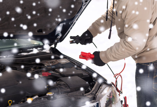 closeup of man under bonnet with starter cables