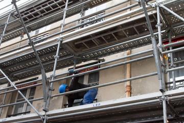 Echafaudage devant une maison en restauration avec un ouvrier