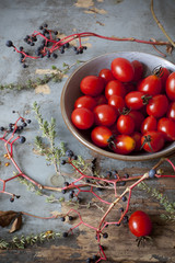 cherry tomatoes on bowl on table with branches and thyme sprigs