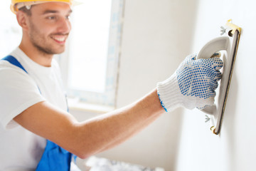 smiling builder with grinding tool indoors