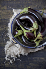group of long eggplants on plate on table with frayed cloth