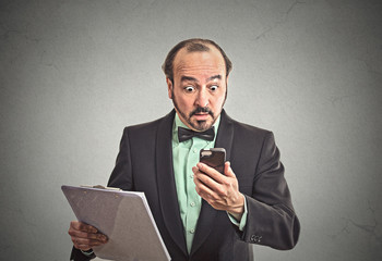surprised business man reading bad news on smartphone