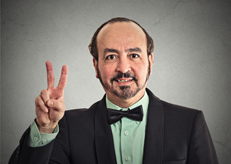 Headshot middle aged businessman smiling with victory hand sign
