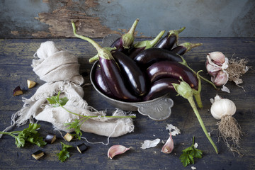 group of long eggplants on wooden table with garlic and parsley