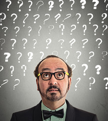 Middle aged man puzzled question marks above head looking up