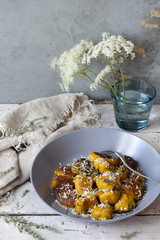 homemade pumpkin dumplings with parmesan on table with flowers