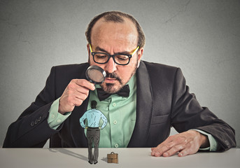 businessman looking at small employee through magnifying glass