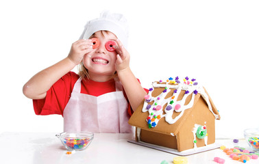Girl Decorating a Gingerbread House  with Candy Over her Eyes