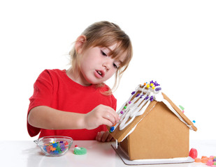 Cute Little Girl Decorating a Gingerbread House for Christmas