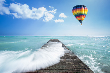 Hot air balloon over the ocean with pathway