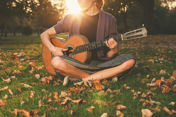 Woman playing guitar in park at sunset