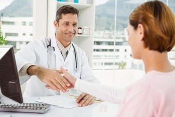 Doctor and patient shaking hands in medical office