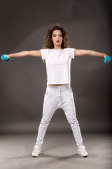 woman doing exercise with dumbbells isolated on gray background
