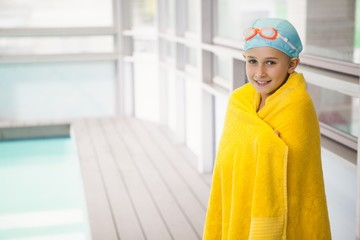 Cute little girl standing poolside wrapped in towel