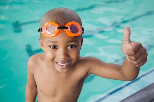 Cute little mixed race boy giving thumbs up at the pool
